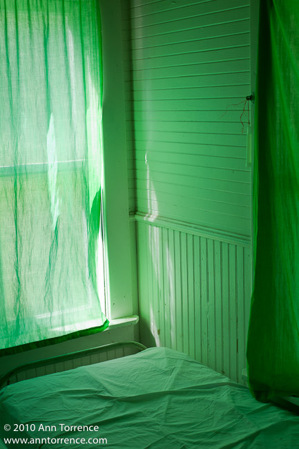 interior of cabin with cot lit through green curtains