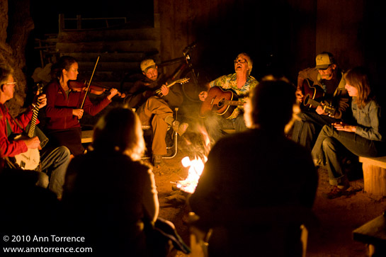 musicians play guitar and violin by campfire light