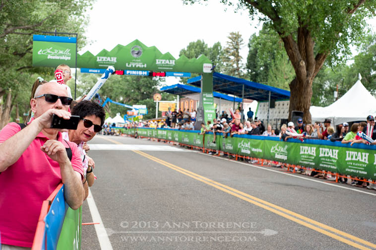 The crowd began to shout and ring bells as the riders, visible on screens set around the street, crested the rise on Utah 24 and sprinted for the finish.