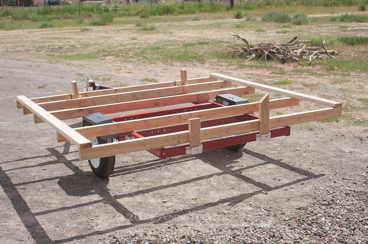 Base built to fit the trailer frame. Width (parallel to axle) is 8'. Length of base is 7'. The frame is temporarily screwed to short pieces of 2x4 in the manufacturer's sleeves provided to install trailer walls