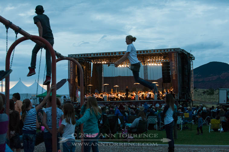Children swing at Teasdale Community Park as the Salt Lake Symphony opens its Mighty 5 Tour on Tuesday August 12, 2014 in Teasdale, Utah.